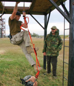 Competitor climbs rope ladder as TJ Piling looks on.