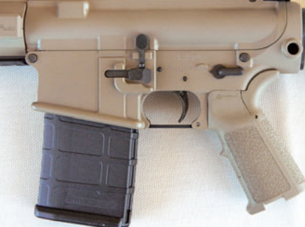 Left side of lower receiver showing ambidextrous magazine release and built-in receptacle for QD sling mount.