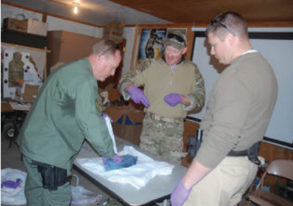 Doc Spears, a former 18D and now a spinal surgeon, supervises students as they learn to pack a gunshot wound in a roast.