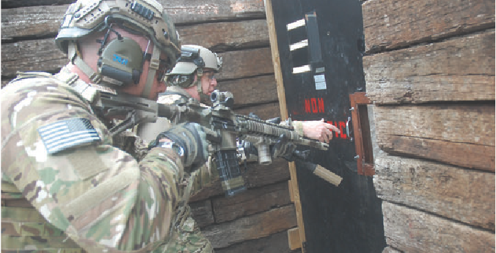 Two U.S. Army shooters show how to properly approach a door. One shooter prepares to open the door while his partner stands ready, covering him and able to engage any threats or move where he needs to. Communication needs to be kept simple, and avoid stating the obvious while under stress.