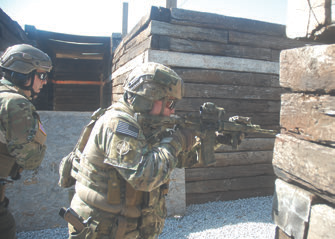 This team demonstrates an L Intersection. Inside shooter starts first, getting his gun up toward any threats covering his partner. Outside shooter moves after inside shooter does, into the hallway and some feet away from the inside shooter. His gun comes up a fraction of a second later. When done correctly, two guns are on a threat at different angles.