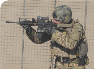 As seen from shooter's left side, thumb and index finger form a C. He is letting the last three fingers of his hand fall naturally against the vertical grip, facilitating a straight pull-back on the rifle into his shoulder. Author prefers a vertical grip to a slick rail because the vertical grip enhances the C-clamp for him. With a slick rail, he tends to pull off to his support-hand side when a lot of tension is applied.