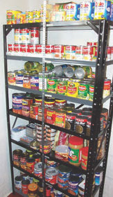 Food supplies can be as close as your local grocery if you rotate your stock. Neatness helps. These supplies are well organized: glass on bottom shelves, shelf unit secured to ceiling with plumber's tape, shelves mounted lip-up, and in a clean, accessible area. Similar stashes in protective containers should be dispersed to other remote but accessible locations. Photo: courtesy www.thenewsurvivalist.com