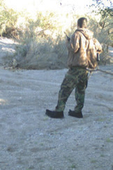 Cartel scout surveys his area, radio in hand, binoculars on his right hip, and wearing carpet shoes to hide tracks.