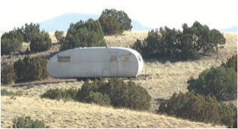 Older trailer tucked in behind a ridge. It's still usable as a shelter.