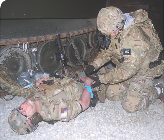 Medic prepares to place IV in casualty's hand under night vision with PVS-14s and Battleview during training exercise at Alliance, Ohio Police Department. Photo: Pat Rogers