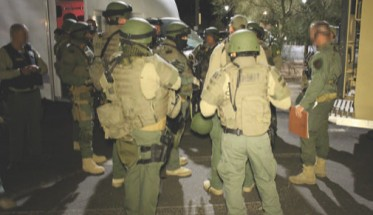Members of Regional SWAT team brief prior to deploying on several cartel stash houses.