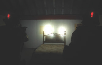 Two shooters enter bedroom in Appling, Georgia shoot house. They both wear a red personal identification light on their helmets, which helps instructors keep track of them. On their carbines, both have SureFire Fury lights mounted. Fury provides 500 lumens of light so they can positively identify their target.