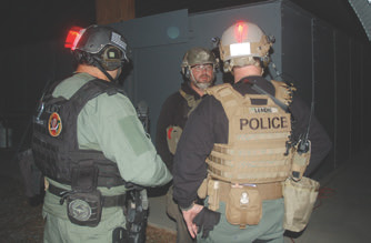 EAG instructor Mike Hueser (Mr. Grumpy) gets brief back from two hard Maryland cops. They have made ready, including their PID, weapon-mounted and handheld lights. They'll brief back the scenario to Mike so that he and the other instructors are satisfied that they know the scenario and who will be in the house with them. Ad hocery does not work in this environment and only leads to disaster down the line.