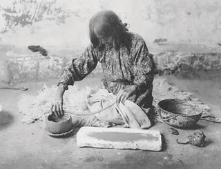 A hundred years ago, this Zuni potter captured the complete essence of coil-built ceramics for photographer Edward S. Curtis. Softened clay is rolled into ropes on flat stone, then deftly used to build a stack of coils in the desired shape. In-place coils are smoothed inside and out as work progresses. Bowl of water at her left is used to keep hands wet and clay moist. New pot sits in shallow dish, which can be rotated to facilitate coiling and smoothing. Some aboriginal African potters use such a dish almost like a potter's wheel. Photo: Edward S. Curtis, via Library of Congress