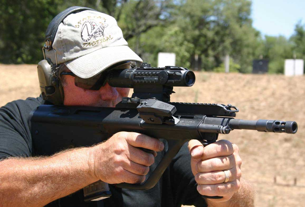 Jim Smith shooting AUG equipped with Leupold CQT optic and Digital Kinematics electronic shooting training device on side rail.