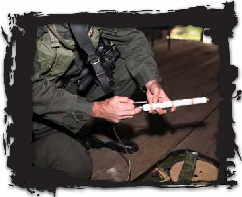 Jungla demolitions expert prepares tube of ANFO explosive while rigging jungle lab to be destroyed. In cocaine lab demolitions, operators use C4, TNT and ANFO as primary explosives.