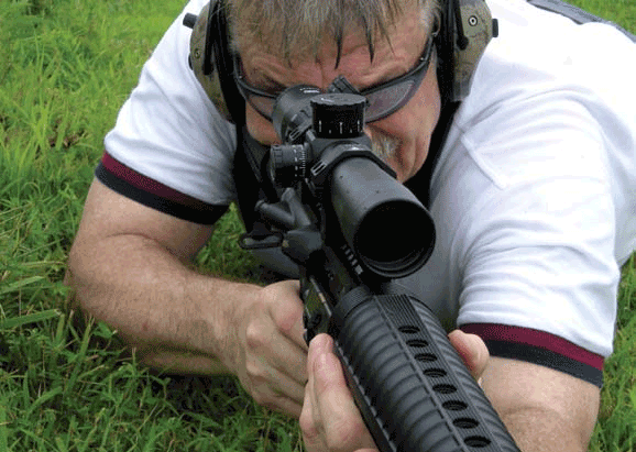 "Thompson firing Rock River Arms LAR-8 with IOR Spartan. Note clearly marked ranging to ""8"" (800 yards) on elevation dial. Humidity is so high that Thompson's glasses have fogged, but Spartan's lenses did not."