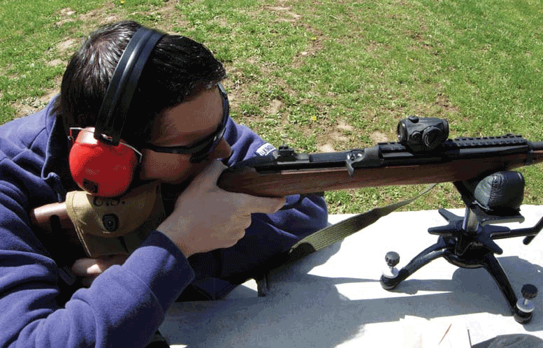 Author's son zeros Auto-Ordnance M1 Carbine at 75 yards with Aimpoint T-1 and Speer Gold Dot ammo. Auto-Ordnance uses original flip-type rear sight.
