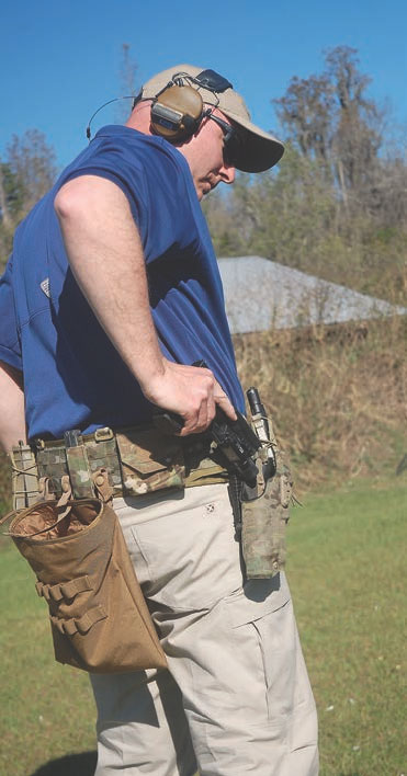 Wade Lynton of the Evans Group glances at his holster to ensure the pistol goes in smoothly. It is a glance, not a long loving look. The pistol only goes back in the holster after your problem is solved.