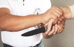 … then places his controlling hand over the thumb and secures the attacker's wrist.
